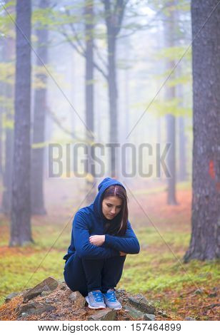 Depressed woman standing alone in forest in autumn