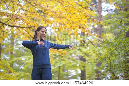 Energetic young woman do exercises outdoors in park to keep their bodies in shape. Fitness concept. Body-building theme. Sport mood.