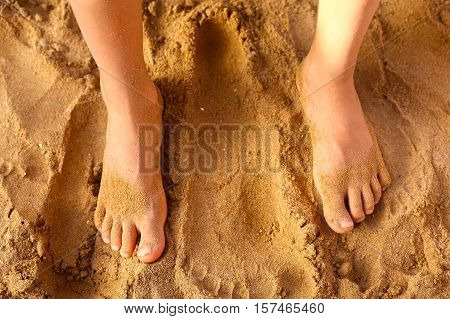 kids foot on the beach sand as a therapy against patypodia flat foot