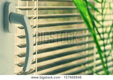 New modern plastic window and interior rooms. Blinds in a home catching the sunlight.