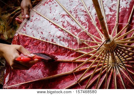 Asian woman hands painting a paper and bamboo umbrella with red color