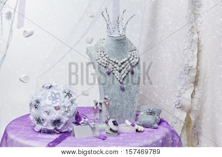 Beautiful set of natural stone bridal accessories including necklace, ring, earrings, bracelets, princess crown and wedding bouquet. Copy space.