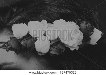 Girl with flowers in her hair on a dark background.