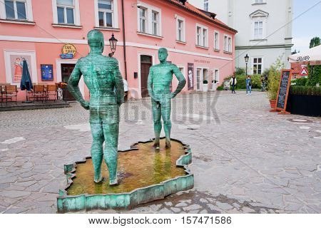 PRAGUE, CZECH REPUBLIC - JUNE 15, 2014: Touristic landmark fountain with two adult pissing men with in water near the popular museum of the writer Franz Kafka on June 15, 2014. Prague receives 4.4 million visitors annually