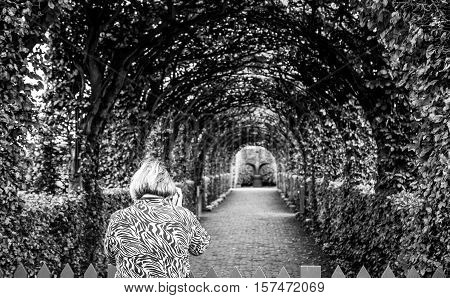 Black-white photo of old woman which photographs park. Muiderslot castle ancient park ensemble in Muiden Noord-Holland The Netherlands.