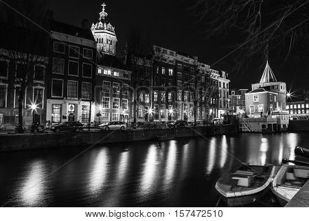 AMSTERDAM NETHERLANDS - DECEMBER 14 2015: Black-white photo of general view night canals in Amsterdam Netherlands.