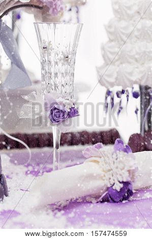 Beautiful crystal champagne glass decorated with purple flowers standing on dessert table