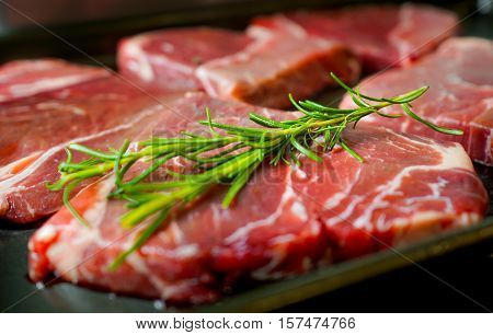 Raw Beef Steak with rosemary leaf spices.