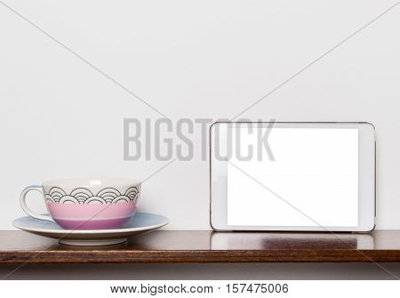 Pastel Tea cup with Blank white tablet screen.