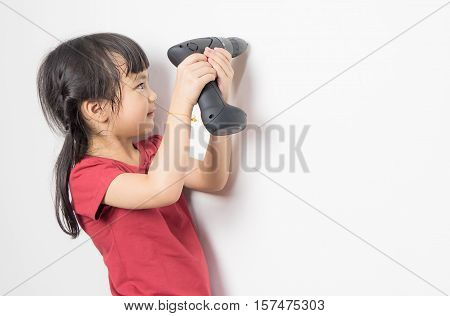 Little asian girl is using screwdriver to fix the wall