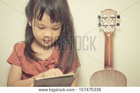 little girl is learning how to play guitar on Internet using her tablet