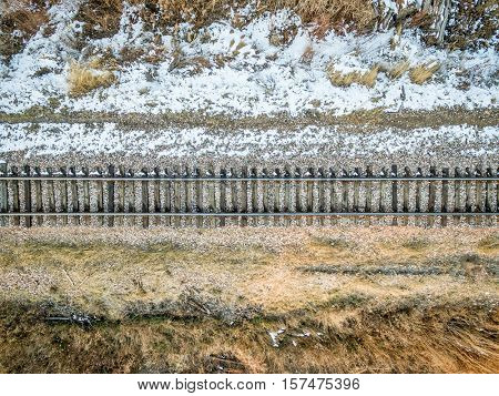 aerial view of single railroad tracks in back country with some weeds and snow