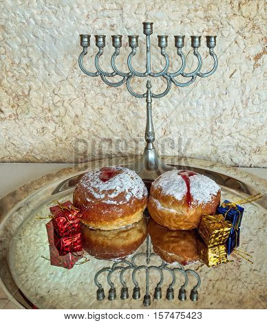 Festive sweet donuts and menorah are traditional symbols of Hanukkah holiday. Selective focus. Image toned for inspiration of retro style