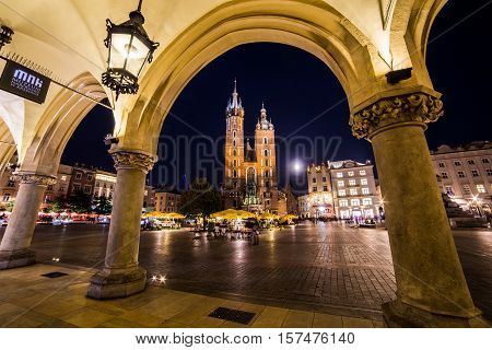 KRAKOW POLAND - 15TH OCTOBER 2016: St. Mary's Basilica shops and buildings on Rynek Glowny (Main Square) in Krakow at night. The blur of people can be seen.