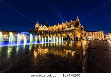 KRAKOW POLAND - 15TH OCTOBER 2016: The Cloth Hall on Rynek Glowny (Main Square) in Krakow at night with the Fontanna na Rynku Głownym. The blur of people can be seen.