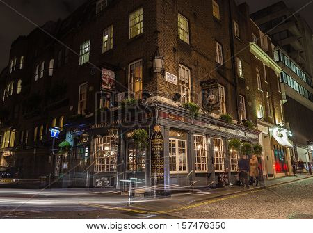 LONDON UK - 8TH OCTOBER 2016: The outside of Shepherds Tavern pub in Mayfair London at night. People can be seen.