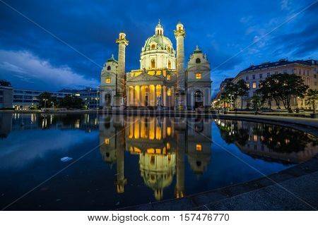 VIENNA AUSTRIA - 3RD OCTOBER 2016: The outside of Karlskirche in Vienna at night. Reflections can be seen in the pond.