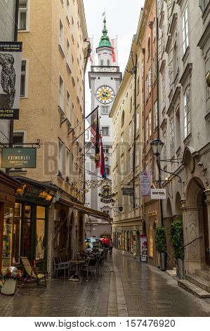 SALZBURG AUSTRIA - 17TH SEPTEMBER 2016: A view of streets in central Salzburg during the day. The outside of shops people and a clock tower can be seen.