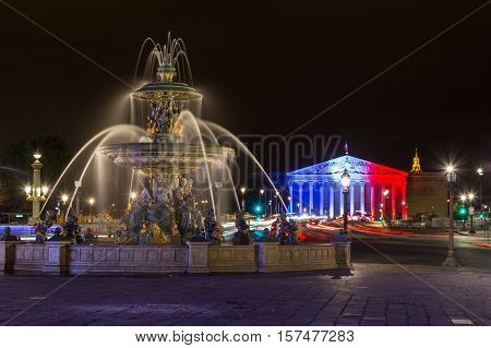 PARIS FRANCE - 28TH JULY 2016: Fontaine des Mers at night. Palais Bourbon with the French Flag illuminated on it can be seen in the distance.