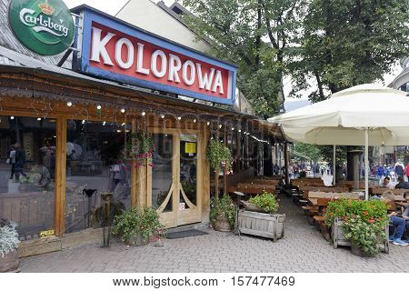 ZAKOPANE POLAND - SEPTEMBER 20 2016: Restaurant named Kolorowa located in the large wooden building at main shopping area and pedestrian promenade in the downtown.