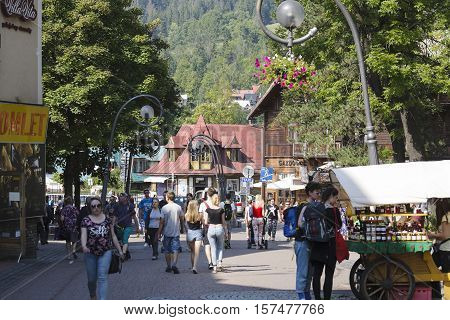 ZAKOPANE POLAND - SEPTEMBER 12 2016: Unidentified people in crowds they walk down the street Krupowki. In the distance the mountain style roof of the old wooden dwelling house can be seen.