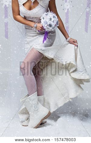Bride in wedding felted gown holding crystal bouquet. Close-up of female legs in white stockings and wool felted boots. Copy space.