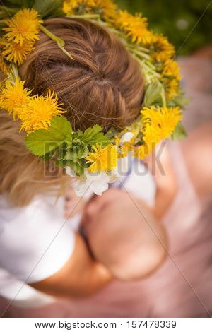 Top view on the mother in a summer wreath of dandelions holding her little baby boy. Mom with newborn baby in the park on a summy day.