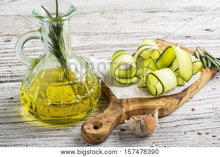 Thin slices of fresh zucchini on the cutting board of the olive tree on a simple wooden table with a bottle of olive oil for cooking homemade spring afternoon. The concept of home seasonal simple natural food. selective focus