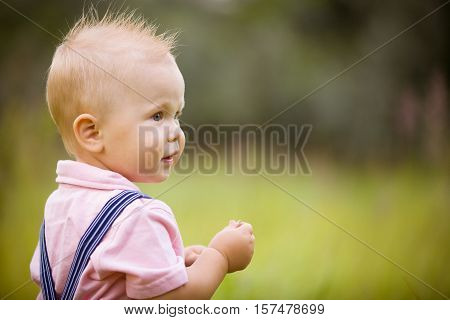 Portrait of cute little blond toddler boy looking into distance. Adorable child walking in the park on a sunny summer day. Summertime. Outdoors. Childhood and lifestyle concept.