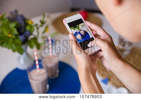 Woman taking photo of many glasses of fresh cold vanilla and chocolate smoothies with straws on table with flowers. Telephone photo of table setting for breakfast. Healthy snacks. Drinks for health.