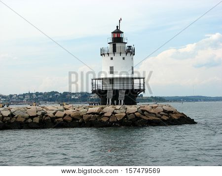 A lighthouse on a peninsula on the shoreline of the Atlantic ocean.