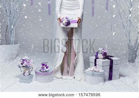 Winter bride in felted dress holding present box decorated with purple art clay flowers. Copy space.