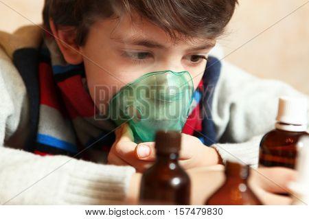 preteen handsome boy with inhalator inhale seam medicine against flu