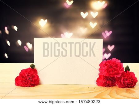 Blank message card with carnation flowers and heart shaped lights