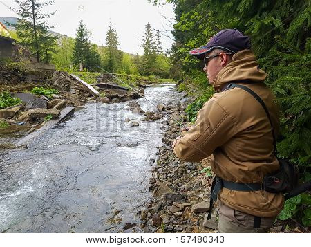 A fisherman caught trout on the mountain river
