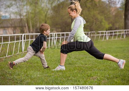 Happy son and mother are doing exercises in the summer park. on the stadium outdoor. Sport activities with children. Healthy lifestyle. Fitness exercises. Young mother and son are stretching together