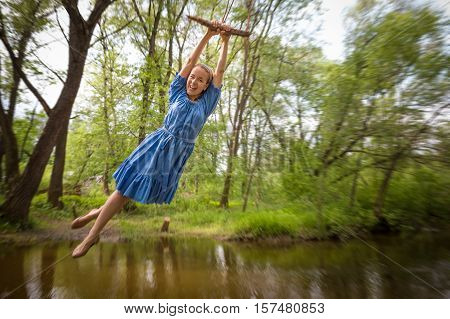 Young beautiful woman in blue dress flying on the bungee above lake in a summer park.