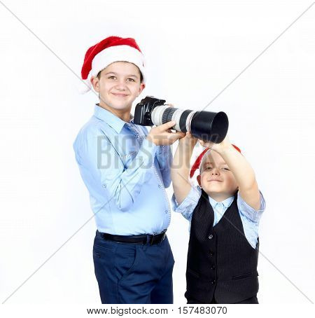 Two brothers in caps of Santa Claus are keeping a camera in his hands