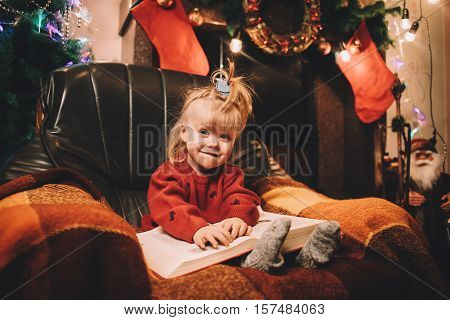 Little smiling girl reading a bedtime story by the fireplace. Pre-christmas mood. New Years is soon