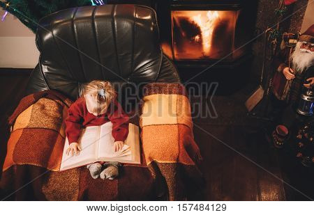 Little girl reading a bedtime story by the fireplace. Pre-christmas mood. New Years is soon
