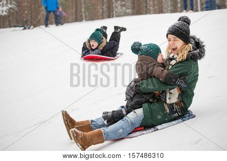 Mother and little toddler boy sliding down the hill in the winter forest and having fun with snow. Family enjoying winter. Child and woman outdoors. Winter Christmas and lifestyle concept.