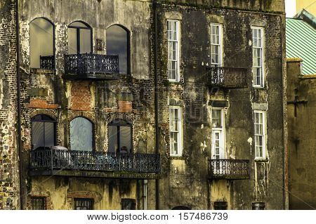 Exterior of a Savannah historic riverfront building. Old wrought iron balconies and old decaying brick work.