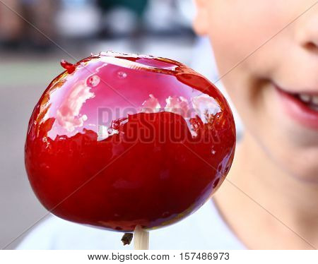 pretty teenage girl with candy red caramel apple close up photo