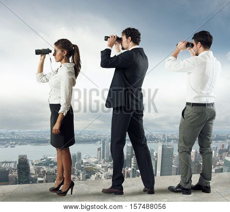 Business people looks at the city from the roof with binoculars