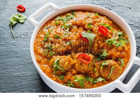 Spicy lentil and meatball soup with parsley. White casserole on black stone background.