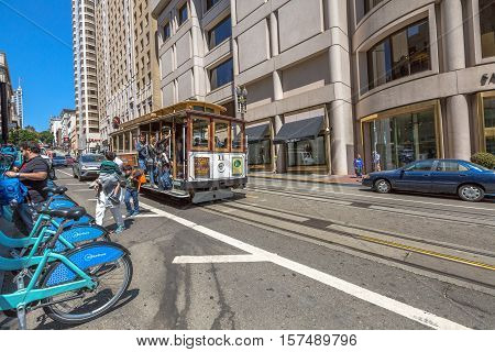 San Francisco, California, United States - August 17, 2016: The popular Cable Car of San Francisco, Powell-Hyde Lines, full of tourists, near Union Square. On roadside a row of typical bike rental.