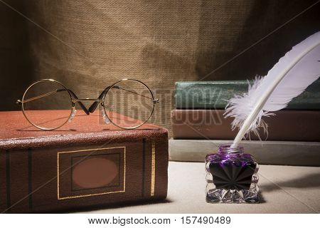 Vintage still life with glasses on old book near inkstand and feather on canvas background.