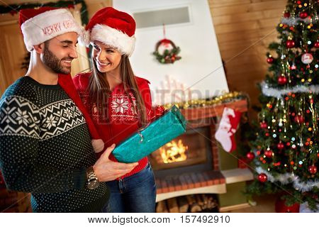 Young couple giving gifts for Christmas