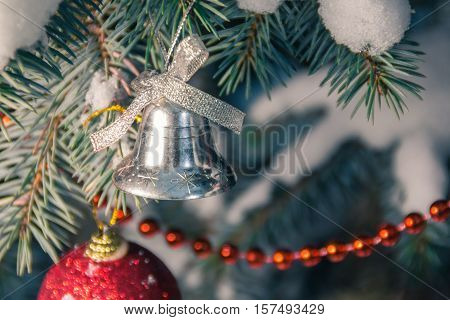 Spruce branch in snow with christmas bell in soft focus