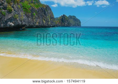 Beautiful tropical beach. Scenic landscape with sandy beach sea and mountain island El Nido Palawan Philippines Southeast Asia. Sea bay scenery. Popular landmark tourist destination of Philippines